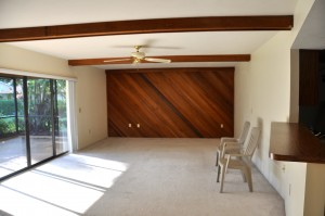 View of living room with the '80's' wood beams and funky wood wall.