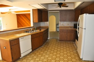 Old kitchen complete with bad linoleum, fake wood countertops and ugly cabinets.